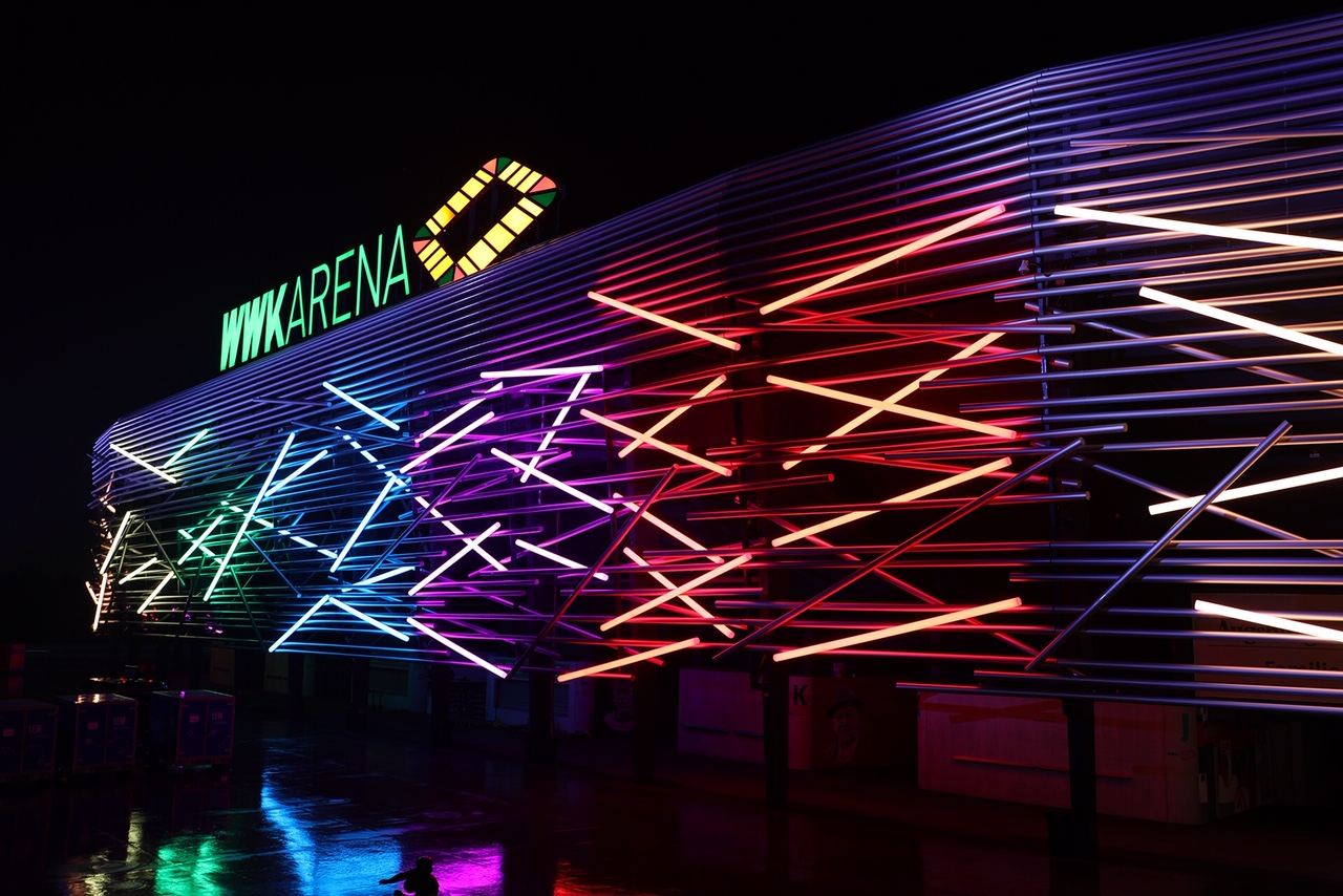 WWK ARENA glowing in a colorful light
